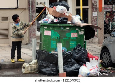 A kid search for food in a garbage on the streets of Thessaloniki, Greece, due to Municipality workers strike on Dec. 17, 2012