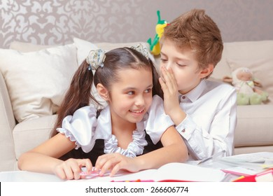 Kid secrets. Close-up of cute school boy whispering something to the ear of a smiling girl