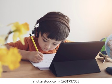 Kid self isolation using tablet for his homework,Child doing using digital tablet searching information on internet during covid 19 lock down,Home schooling,Social Distance,E-learning online education - Shutterstock ID 1681937335