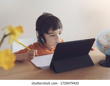 Kid self isolation using tablet for his homework,Child doing using digital tablet searching information on internet during covid 19 lock down,Home schooling,Social Distance,E-learning online education