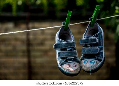 Kid shoes hanging on the loundry rope outdoor.