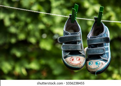 Kid shoes hanging on loundry rope. outdoor.  Childrens blue sneakers