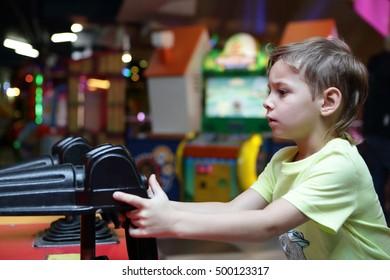 Kid shooting a gun in an amusement park