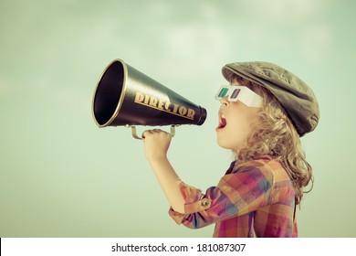 Kid shouting through vintage megaphone. Communication concept. Retro style