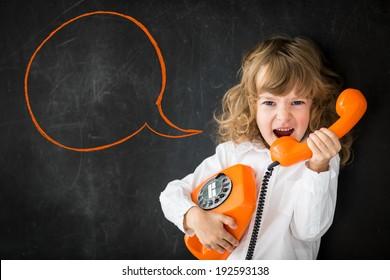 Kid shouting through vintage phone. Business communication concept