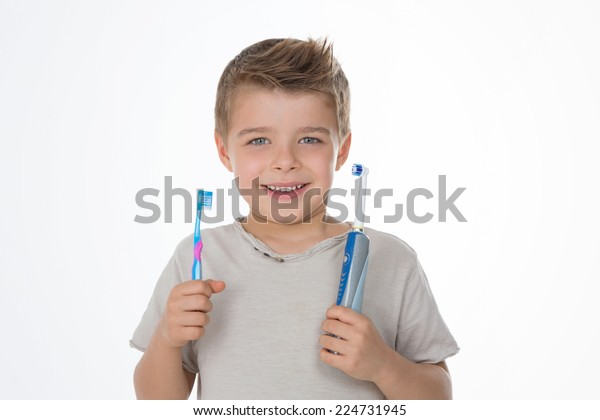 kid shows his manual and electric toothbrushes