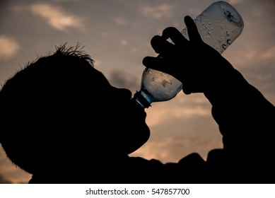 A kid silhouette drinking water on sunset