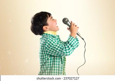 Kid singing over ocher background