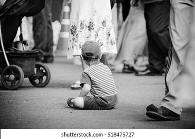 Kid siting on floor on street. Lost kid. Black and white