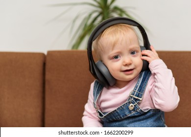 Kid sits in the headphones and smiles. Baby listens to music.