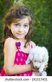 kid sitting and holding puppy