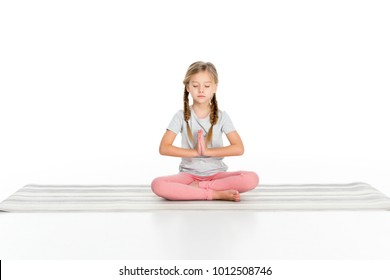 kid sitting in lotus position on yoga mat isolated on white