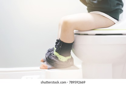 Kid sitting on toilet, Low view on his legs hanging with black jean with fluffy sock in retro tone, copy space, Training child or Health care concept.