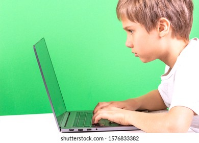Kid sitting at the table and using laptop computer, light green background