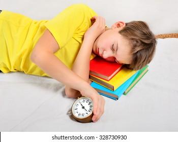 Kid sleep with Alarm Clock on the Books