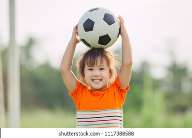 Kid with smiling face playing soccer football in the sunshine day.