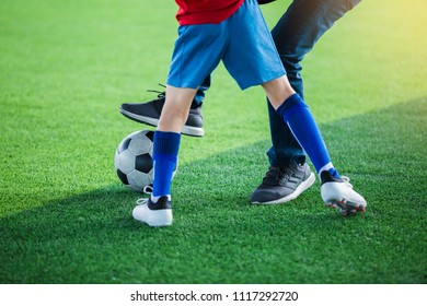 Kid soccer and dad are playing ball on at artificial turf.