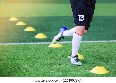 Kid soccer Jogging between yellow marker cones for soccer training of academy.