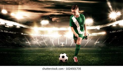 Kid - soccer player. Boy forward in football sportswear on stadium with ball. Sport concept.