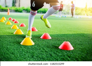 Kid soccer player moving speed test and Jogging and jump between marker for football training.