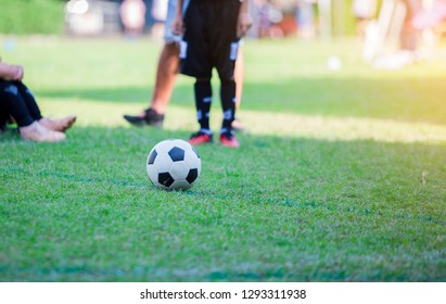 Kid soccer player speed run to shoot ball to goal on green grass. Soccer player training for football match.
