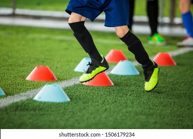 Kid soccer players jogging between marker cones on green artificial turf for training. Football or soccer academy.
