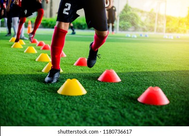 Kid soccer players Jogging and jump between cone marker for football training.