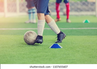 Kid soccer trap and control the soccer ball between marker cones.
