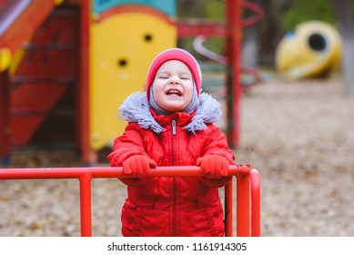 the kid is spinning on a swing in the playground in the park