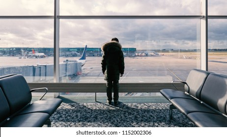 Kid standing inside waiting room and looking at the window at planes in international airport. Conceptual image for traveling, vacation.