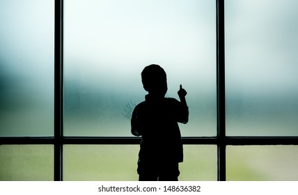 Kid standing and plays on window