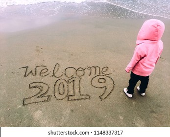 Kid standing starting to an open sea with a text welcome 2019