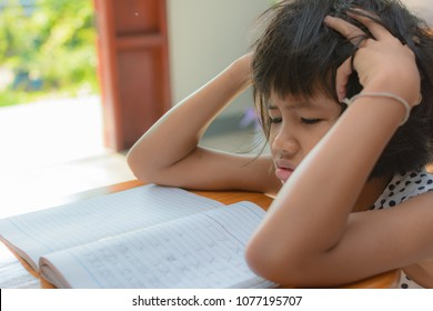Kid struggling with homework , she used her hand to face palm. Can used for concept of the education system is making kids stressed and sick.