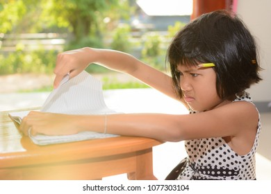 Kid struggling with homework , she used her hand to tear the book. Can used for concept of the education system is making kids stressed and sick.