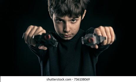 Kid studio portrait against black background holding two guns.