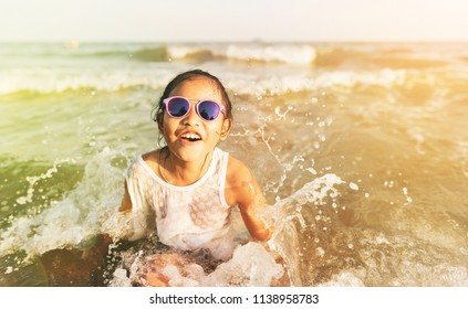 Kid with sunglasses having fun and enjoys summer day at the beach.Asian little girl playing with waves.Happy child playing in the sea with Summer vacation and healthy lifestyle concept