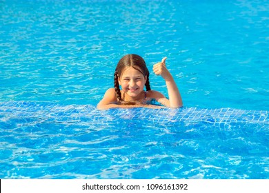 Kid swims in the pool. Smiling child leads a healthy lifestyle and keen on sports. Child shows thumb up symbol. Summer holidays, children's swimming, summer vacation concept.