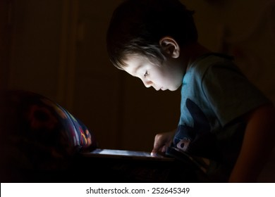 kid with tablet in the dark laying in bed and reading