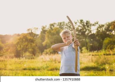Kid targeting with wooden arrow at something while playing outside at sunny sunset nature background. Horizontal color photography.