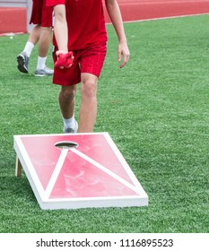 A kid is throwing a bean bag during a game of corn hole on a turf field outside.
