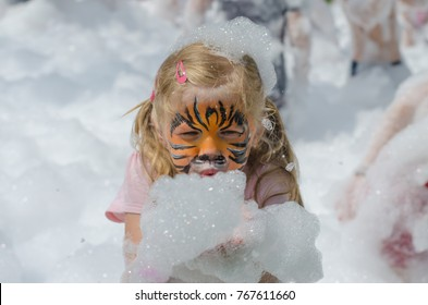 kid with tiger face painting in foam