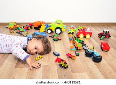 Kid tired after playing with so many toys. Toddler sleeping on the floor, surrounded by lots of cars toys