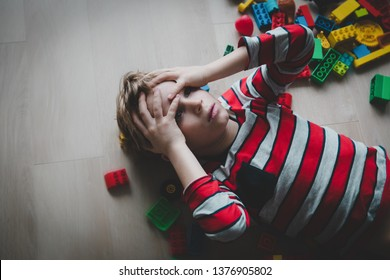 kid tired of playing, exhaustion with toys scattered around