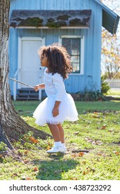 Kid toddler girl with branch stick playing outdoor park latin ethnicity