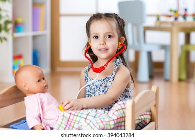 Kid toddler playing doctor role game examining her doll using stethoscope sitting in playroom at home, school or kindergarten