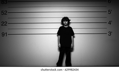 KID IN TROUBLE.  BLACK AND WHITE SHOT OF A YOUNG BOY IN A POLICE LINE UP.  MODEL RELEASE.