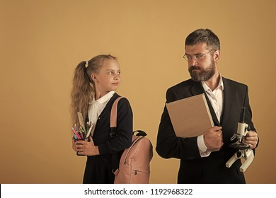 Kid and tutor hold book, pencils and microscope. Girl with bag and bearded man. Education and back to school concept. Teacher and schoolgirl with happy or confident faces on orange background