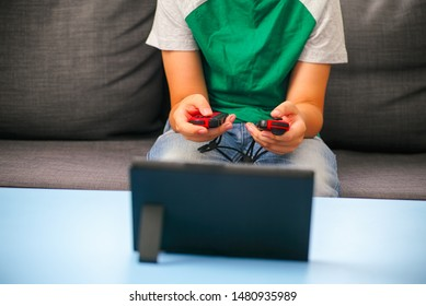 Kid with two gamepads playing video game console indoors.