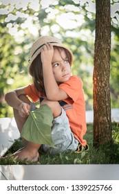 Kid under tree with leaf