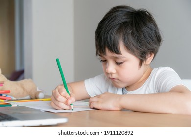 Kid with unhappy face doing homework, Bored Child using green pencil colouring, Young Boy is drawing or painting on white paper, Concept for homeschooling, Learning online education at home